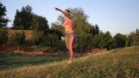 Fitness hipster girl in fashion sportswear doing yoga fitness exercise in the street, outdoor sports. Fitness hipster girl in fashion sportswear doing yoga stock video