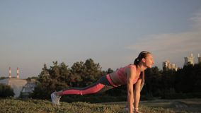 Fitness hipster girl in fashion sportswear doing yoga fitness exercise in the street, outdoor sports. Fitness hipster girl in fashion sportswear doing yoga stock video footage