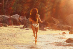 Fitness holidays. Beautiful girl runs along the beach Royalty Free Stock Images