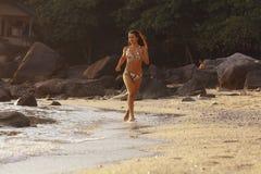 Fitness holidays. Beautiful girl runs along the beach Royalty Free Stock Image