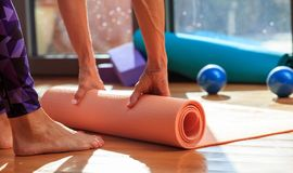 Woman rolling a yoga mat on wooden floor Royalty Free Stock Photography