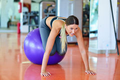 Fitness, home and diet concept - smiling girl exercising with fitness ball at gym Royalty Free Stock Images