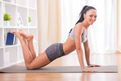 Fitness at home. Pretty woman is doing fitness at home on her living room floor. Fitness, workout, healthy living and diet concept Royalty Free Stock Image