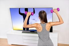 Home fitness woman strength training watching TV. Fitness at home woman working out watching tv. Back of a young sporty girl following workout videos online on royalty free stock photos