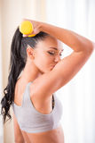 Fitness at home. Young woman is exercising with dumbbells at home. Fitness, workout, healthy living and diet concept Stock Image
