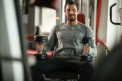 Free Fitness In Gym, Sport And Healthy Lifestyle Concept. Handsome Athletic Man In Grey Shirt Making Exercises. Bodybuilder Stock Photos - 185374483