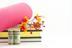 Fitness industry success symbolized in yoga mat, books, flowers, Royalty Free Stock Photography