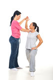 Fitness instructor assisting woman Royalty Free Stock Images