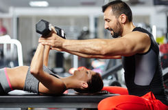 Fitness instructor assisting young woman Stock Photos