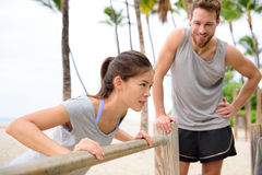 Fitness instructor coaching woman doing push-ups. Fitness instructor coaching and helping women doing push-ups on cross fit horizontal bar station on beach. Arm Stock Image