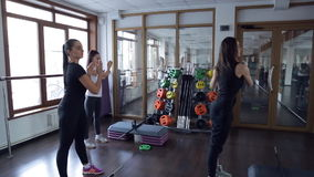 Fitness instructor demonstrates exercises to clients next to mirror stock video footage