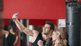 Fitness instructor doing mobile selfie with woman boxer after training. stock footage