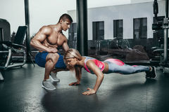 Fitness instructor exercising with his client at the gym. Royalty Free Stock Photography