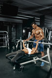 Fitness instructor exercising with his client at the gym. Stock Photos