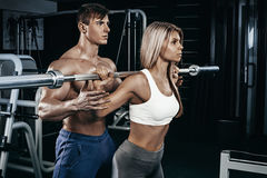 Fitness instructor exercising with his client at the gym. The beautiful blonde is engaged in sports. Handsome man, sports instructor stock image