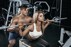 Fitness instructor exercising with his client at the gym. Royalty Free Stock Photo