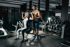Fitness instructor exercising with his client at the gym. Stock Photo