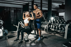 Fitness instructor exercising with his client at the gym. Stock Image