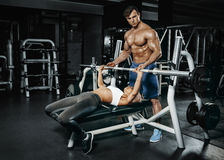 Fitness instructor exercising with his client at the gym. Royalty Free Stock Image