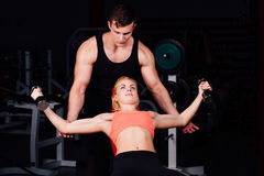 Fitness instructor exercising with his client at the gym. Stock Images