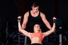 Fitness instructor exercising with his client at the gym. Royalty Free Stock Images