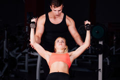 Fitness instructor exercising with his client at the gym. Stock Photography