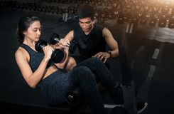 Fitness instructor exercising with his client at the gym, Personal trainer helping woman working with heavy dumbbells stock photo