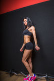 Fitness instructor. Wearing black sports bra, shorts and pink and blue trainers standing showing off muscular body against black background royalty free stock photos