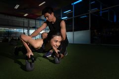 Fitness instructor with girl on training in fitness center, Shot of young woman doing push-ups at the gym. Muscular female doing p royalty free stock images