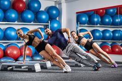 Fitness instructor and girls side planking. Side planking fitness trainer with girls Stock Images