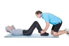 Fitness Instructor Help Woman Doing Exercise Stock Image