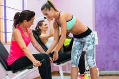 Fitness instructor helping cheerful woman to straighten her back Stock Photos