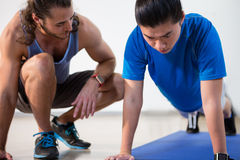 Fitness instructor helping fitness man with push-up Stock Photography