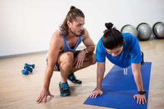 Fitness instructor helping fitness man with push-up Stock Image