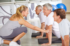 Fitness instructor helping senior people in gym. During back training class Royalty Free Stock Images