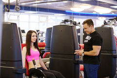 Fitness instructor helps girl to choose exercise Royalty Free Stock Photo