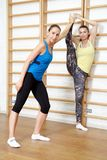 Fitness instructor helps to do exercise on an extension Royalty Free Stock Images