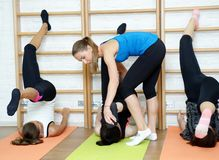 Fitness instructor helps to do exercise on an extension Stock Images