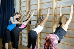 Fitness instructor helps to do exercise on an extension Royalty Free Stock Photography