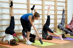 Fitness instructor helps to do exercise on an extension Stock Photos