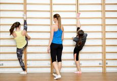 Fitness instructor helps to do exercise on an extension Royalty Free Stock Photos