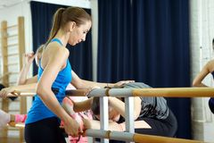 Fitness instructor helps to do exercise on an extension Stock Photo