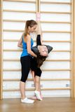 Fitness instructor helps to do exercise on an extension Royalty Free Stock Image