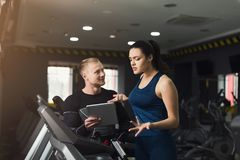 Fitness coach helps woman on elliptical trainer stock images