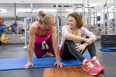 Fitness instructor and mature woman at gym. Female sports instructor and middle-aged woman talking smiling and laughing in health. Fitness instructor and mature royalty free stock images