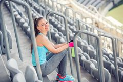 Fitness instructor resting and excercising. sportswoman enjoying a good, quality workout on stadium stairs Royalty Free Stock Images