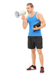 Fitness instructor shouting on a megaphone. Full length portrait of a fitness instructor shouting on a megaphone isolated on white background Royalty Free Stock Images