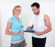 Fitness instructor taking notes after a session Royalty Free Stock Image