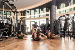 Fitness instructor timing lateral crunch exercise with raised le. Fitness instructor timing three young people doing lateral crunch exercise with raised legs for Stock Photography