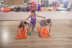 Fitness instructor training correcting  push up group three peop Royalty Free Stock Images